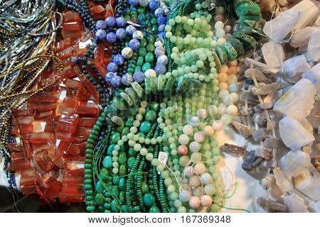 Many colorful necklaces of gems as natural background