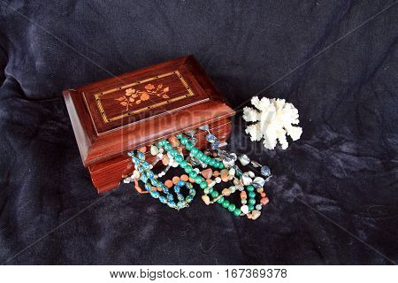 Still life with wood jewelry box and necklaces