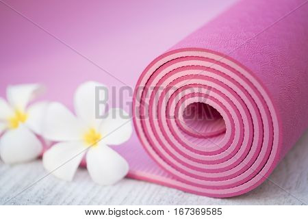 pink yoga mat and a flowers, close up
