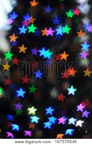 Stars Bokeh Lens Effect on a blurred Christmas tree
