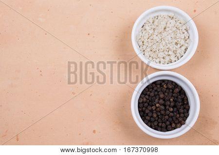 Course Gray Salt And Peppercorns In Smal Ramekins On Saltillo Tile