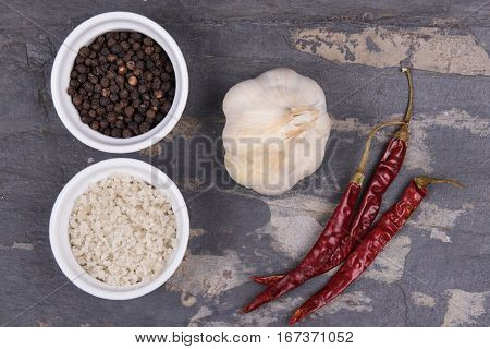 Course Gray Salt, Peppercorns, Garlic Ad Dried Red Peppers On Gray Slate