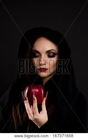 Stepmother witch watching at poisoned red apple