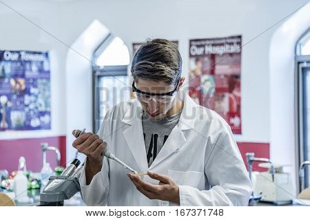 A young man medical or scientific researcher or doctor working with pipette in a laboratory.