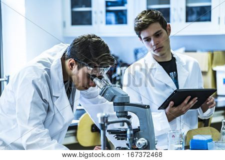 scientific researchers using a microscope in a laboratory environment. Research close-up of a microscope and scientist in white lab coats