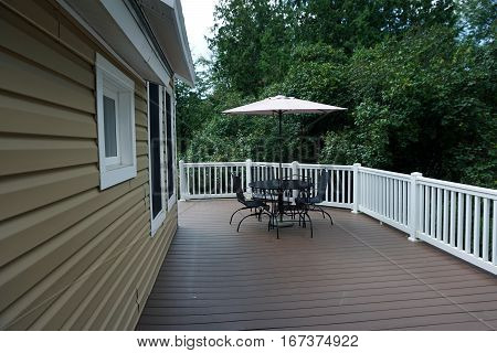 The back deck, with outdoor furniture and an umbrella, of a home in Harbor Springs, Michigan, on a beautiful day in August.