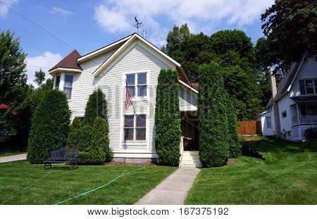HARBOR SPRINGS, MICHIGAN / UNITED STATES - AUGUST 4, 2016: A home with tall, sculpted arborvitae (Thuja occidentalis) bushes flies the American flag.