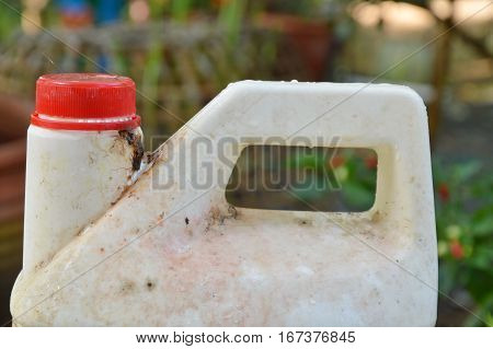 wash chemical with red cover gallon and dirty stain in garden
