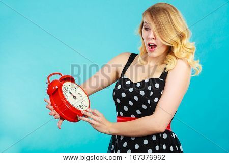 Shocked Girl With Alarm Clock On Blue.