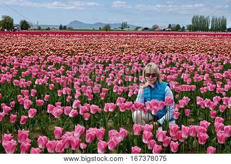 Blond woman on tulip field. Mount Vernon Tulip Festival. Tulip Town. Seattle. Washington. United States.