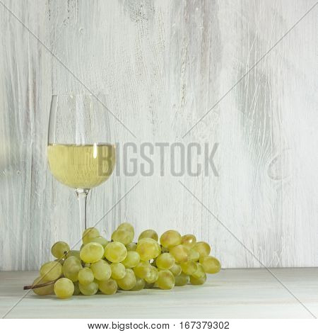 White grapes and a glass of white wine on a wooden background texture with copy space
