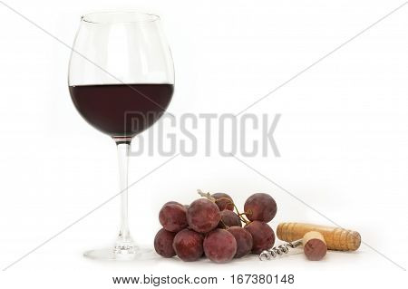 A photo of a glass of red wine with a bunch of grapes, a cork, and a corkscrew, shot from the side on white background