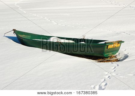 green abandoned boat on lake shore in winter