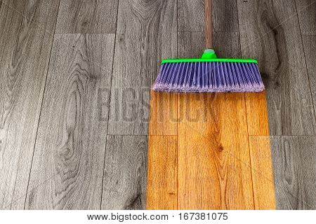sweeping out wooden parquet with green plastic broom