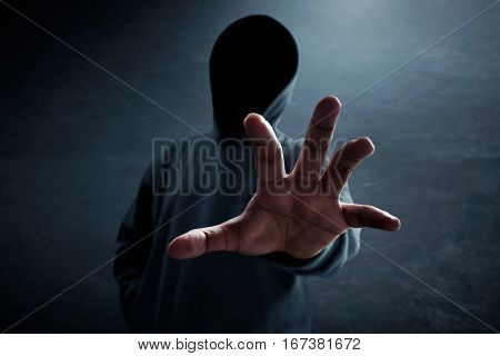 Unknown hacker standing alone in dark room