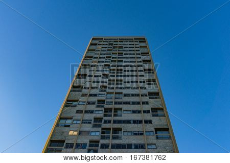 Tall Building With Windows Against Blue Sky On The Background
