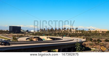 Highway exit headed from Newport Beach into Irvine California USA with white-capped mountains in the distance and a blue sky above.