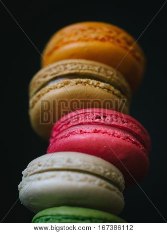 Close-up of colorful macaroons.Stack of sweet macaroons, green, pink and orange color