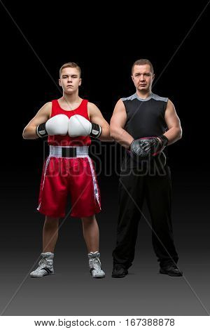 Young teen boxer in blue suit and black gloves working out with boxing coach holding paw. Isolated on white. Copy space.