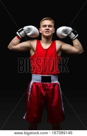 Happy young handsome boxer sportsman in red boxer suit and white gloves standing on black backgound. Winner. Copy space.