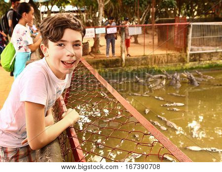 Mekong river, Vietnam, December 27, 2016: Unidentified teen tourist boy feed crocodiles on crocodile farm on one of the islands on Mekong river in Vietnam, December 27, 2016.