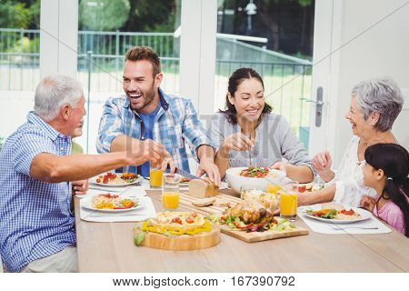 Happy multi generation family having food at dining table in home
