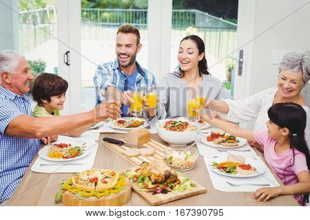 Smiling multi generation family toasting juice at dining table