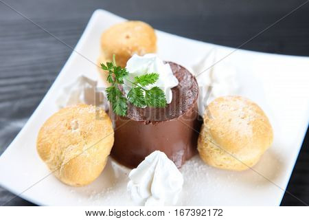 close up shot of chocolate pudding with cream puffs