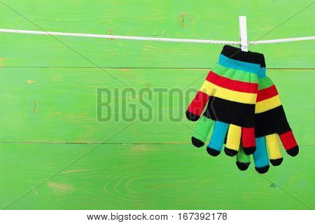 Striped colorful gloves hanging on the clothesline on green wooden background