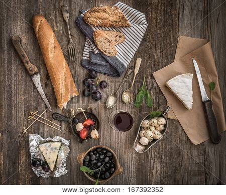 French breakfast. Different types of cheese, wine and other ingredients on a wooden table