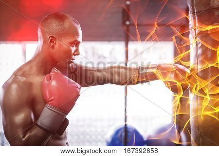 Side view of male boxer punching bag in fitness studio