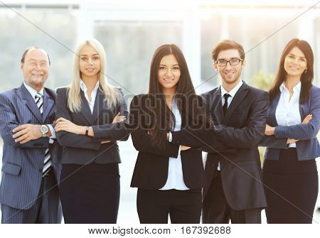 successful and happy business team on office background headed by a woman on a sunny day