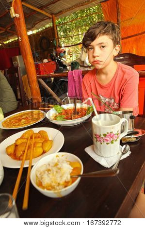 european kid dining in asian cafe in vietnam