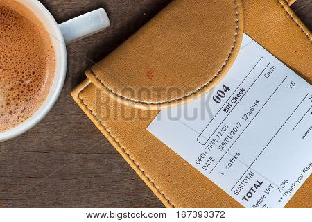 cup of coffee and receipt bill in folder payment on wooden table