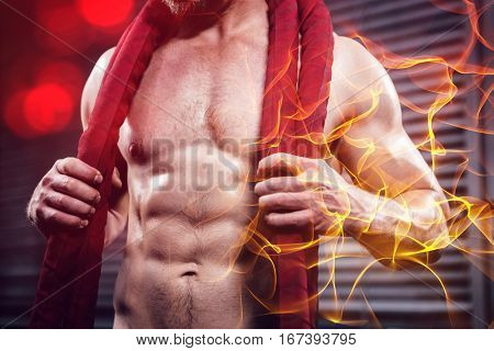 Midsection of shirtless man with battle rope around neck at the crossfit gym