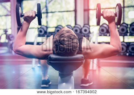 Man lifting dumbbell weights while lying down in gym