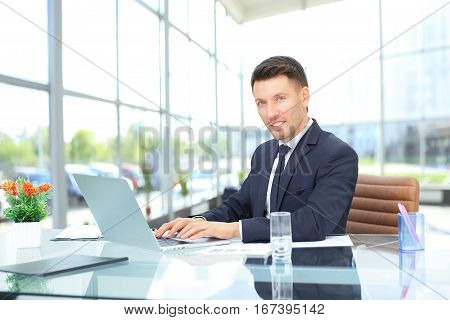 businessman in black business suit sitting behind a Desk in the spacious office