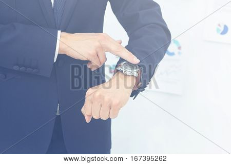 on the left side of the photo close-up of businessman with finger point at his watch in his hand. on the right side of the photo on the background of the financial schedules there is empty space for your text