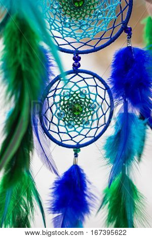 Green and blue Dreamcatcher made of feathers leather beads and ropes hanging
