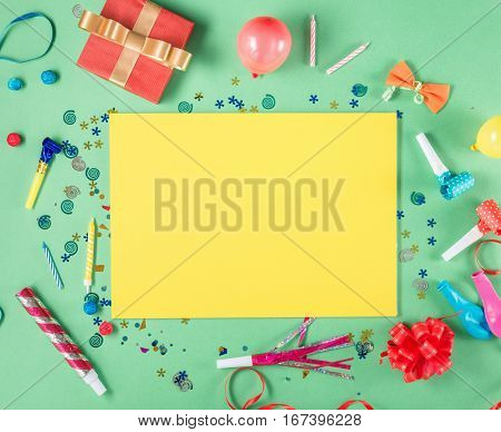 Blank yellow sheet of paper with a red gift box various party confetti balloons streamers noisemakers and decoration. Colorful celebration background. Top view. Flat lay