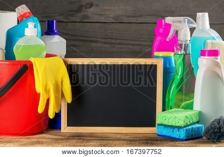 Variety cleaning product with small empty chalk board on wooden table close up