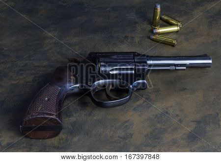 Six shooter loaded gun .38 caliber handgun with wood grip and brass flat head bullets isolated on dark grunge background