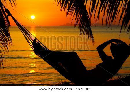 view of a woman lounging in hammock during sunset poster