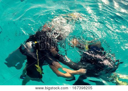 Couple divers plunged into the ocean top view close up