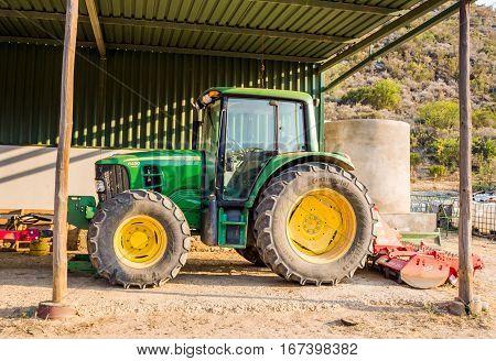 DE RUST SOUTH AFRICA - 22 DECEMBER 2016: Modern John Deere tractor parked in a shed