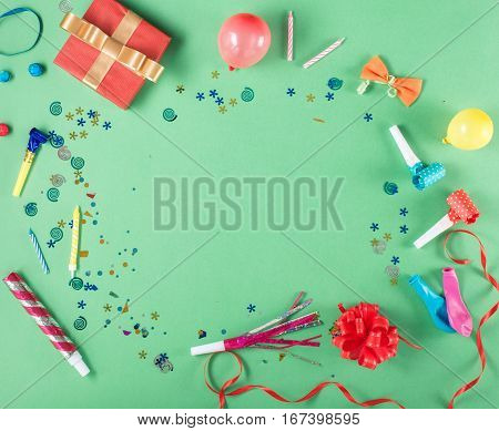 Colorful party frame with red gift box with various party confetti balloons streamers noisemakers and decoration on a green background. Colorful celebration background. Flat lay.