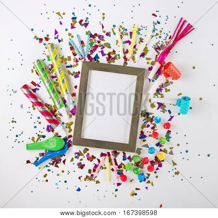 Various party confetti balloons streamers noisemakers and decoration on a white background. Colorful celebration background. Top view. Flat lay.