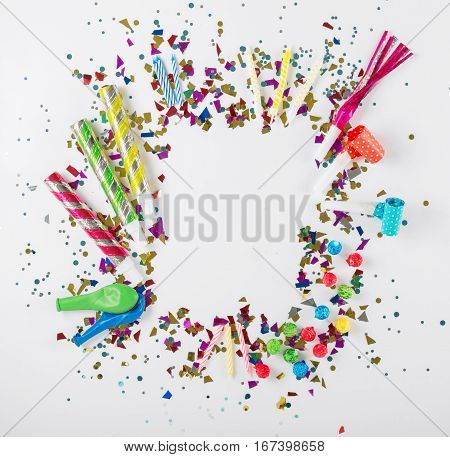 Frame with confetti balloons streamers noisemakers and decoration on white background. Colorful celebration background. Top view. Flat lay