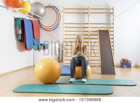 Young sports girl in the gym using a smartphone