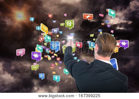 Rear view of young businessman in suit pointing against gloomy sky 3d